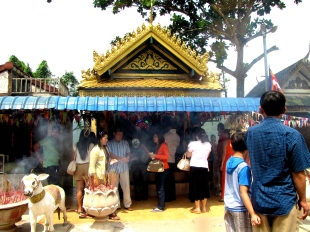Stopping by the crowded altar on Highway 3 to Kampong Som to say a prayer to Grandmother Mao, divine protector of travelers (Note the flashing lotus lights in the background and think: modern technology meets ancient ritual, yeah that's right) - Highway 3 to Kampong Som