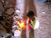 Young boy burning the ubiquitous color paper strip inside Arthaross Temple - Phnom Oudong, Kandal
