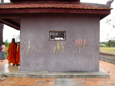 Pieces of faded color paper stuck on the exterior walls of the memorial - Wat Kampong Tralach, Kampot