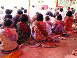 The ladies, finished with preparing the flower decorations, sit sarong-clad, krama-wrapped, and feet propped - Takeo
