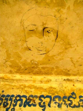 """The faded drawing of a face on an old genocide memorial on site hovers above a Khmer proverb that reads, """"Calming your anger makes you sleep well"""" - Wat Samdech Mony, Battambang"""