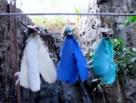 """A variety of decorative memorabilia made of scrap fabrics hang on lines throughout the """"killing caves"""" buried in the mountain - Phnom Sampeou, Battambang"""