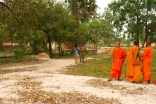 Chin Sen gives context about the history of the mass graves as the local young monks look on - Wat Kampong Tralach, Kampot