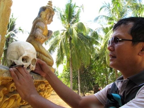 Sak handles one of the skulls exposed in the memorial's second tier encasement - Wat Samdech Mony, Battambang