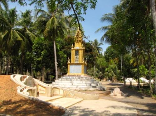 Chinese white stone gravesites dot the area around the Khmer Buddhist style stupa - Wat Samdech Mony, Battambang