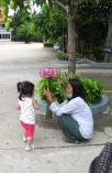 Two-year old curious about this handful of lotus flowers - Wat Champuh Ka'ek, Phnom Penh