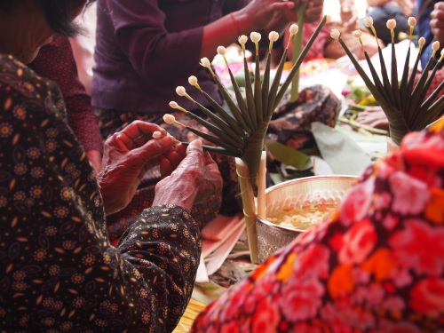 Women from the community gather to cut and fold and tie trinkets of jasmine buds and palm leaves that will lace the premises of the stupa ceremony site - Samroung, Takeo